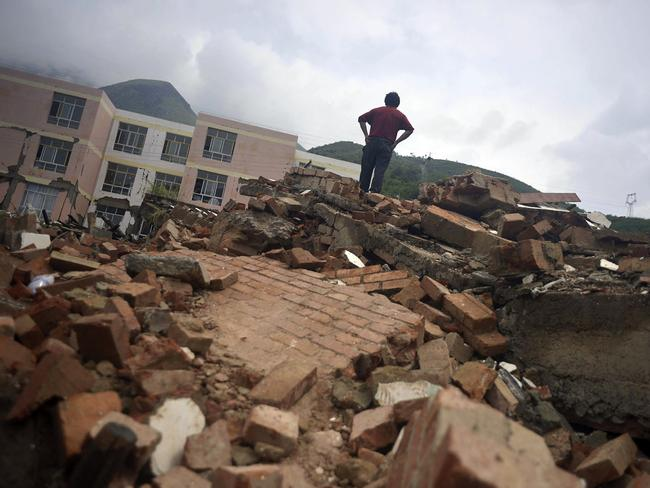 Shatters...A resident stands on remnants of a collapsed building in Longtoushan. Picture: AP