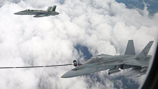 One fighter locks on for refuelling as another holds position in formation with the tanker. Picture: Alex Coppel