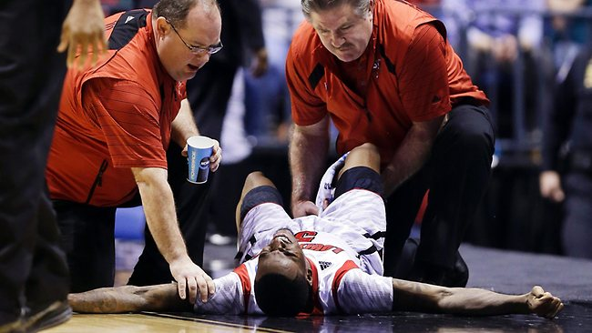 Trainers check on Louisville guard Kevin Ware after Ware injured his lower right leg during the first half of the Midwest Regional final against Duk in Indianapolis. Picture: Michael Conroy