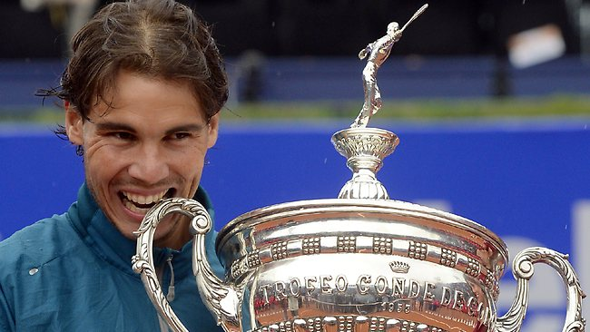 Rafael Nadal bites the trophy after his victory over Nicolas Almagro in the Barcelona final open tennis in Barcelona. Nadal won 6-4, 6-3. Picture: Manu Fernandez