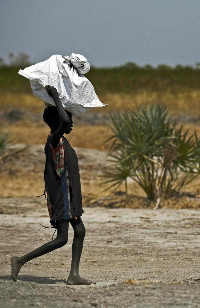 A child carries food air-dropped by the International Committee of the Red Cross outside Thonyor, in South Sudan.