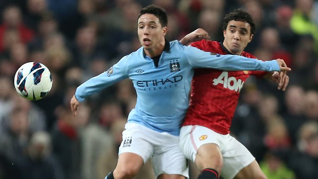 Manchester United's Rafael, right, challenges Manchester City's Samir Nasri in the English Premier League match at Old Trafford. Picture: Jon Super