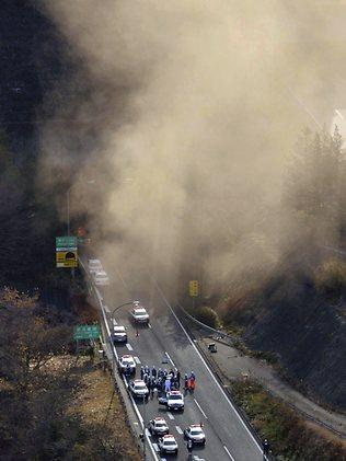 Smoke billows from the entrance of the collapsed Sasago tunnel as police and fire workers gather in preparation for their rescue operation. Picture: AFP