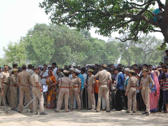 Failed to act ... police cordon off an area around the tree where two teenage girls were found hanging after they were gang raped in the northern Indian state of Uttar Pradesh. Picture: Rajeev Pal