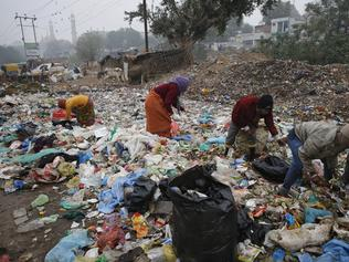 FILE - In this Jan. 21, 2016 file photo, Indian rag pickers look for reusable materials at a garbage dump littered with polythene bags in Lucknow, India. A new massive study finds that production of plastic and the hard-to-breakdown synthetic waste is soaring in huge numbers. The study says since 1950, industry has made more than 9 billion tons of plastics. That's enough to cover the entire country of Argentina ankle deep in the stuff. (AP Photo/Rajesh Kumar Singh)