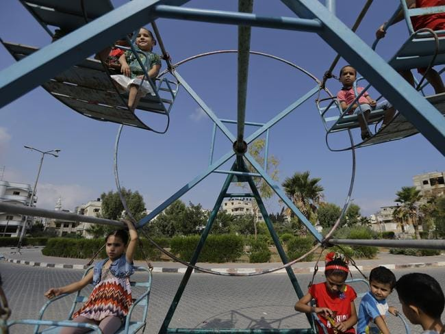 Deserted streets ... Palestinian children ride a swing while celebrating on the first day of the Muslim festival of Eid al-Fitr in Gaza City. Picture: Lefteris Pitarakis