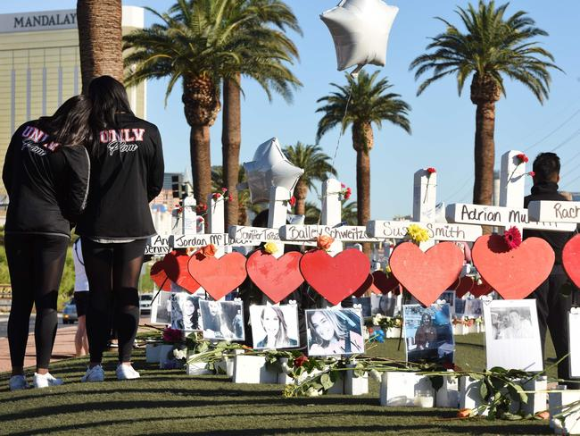 Members of the University of Las Vegas prom squad visit 58 white crosses for the victims of the shooting. Picture: Robyn Beck/AFP