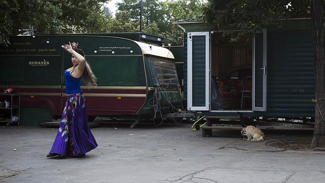 A gypsy circus performer rehearses a dance act outside her aravan in Paris. AFP / Joel Saget
