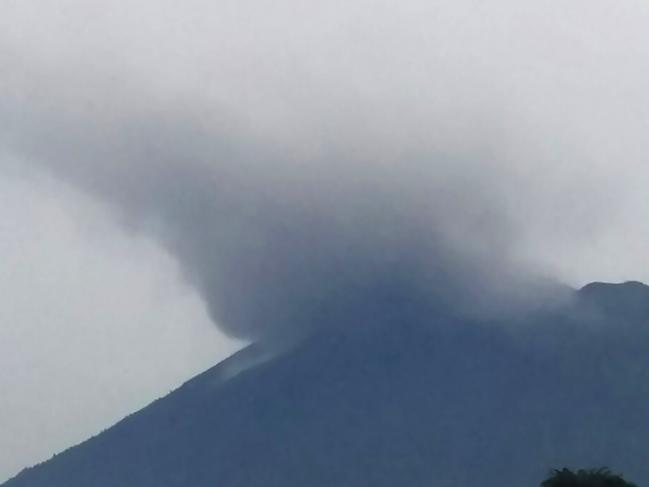 "This handout from Indonesia's Disaster Mitigation Agency (BNPB) taken and released on November 21, 2017 shows Mount Agung volcano spewing smoke in Karangasem on Indonesia's resort island of Bali. A rumbling volcano on the holiday island of Bali spewed ash and towering clouds of smoke on November 21, heightening fears it may erupt for the first time in more than 50 years. Mount Agung belched smoke as high as 700 metres (2,300 feet) above its summit, as it stirred to life again after more than 140,000 people fled homes around the crater last month amid fears the long-dormant volcano would erupt. / AFP PHOTO / BNPB / HANDOUT / RESTRICTED TO EDITORIAL USE - MANDATORY CREDIT ""AFP PHOTO /Indonesia's Disaster Mitigation Agency (BNPB) "" - NO MARKETING NO ADVERTISING CAMPAIGNS - DISTRIBUTED AS A SERVICE TO CLIENTS"