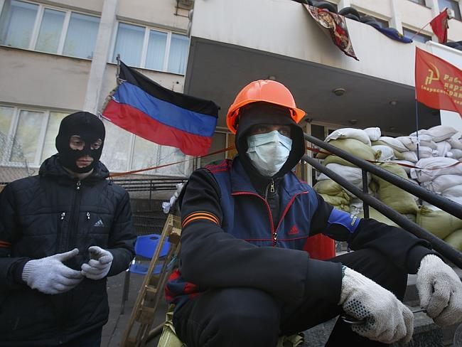 Violence...Masked pro-Russian protesters guard a barricade in front of the city hall in M