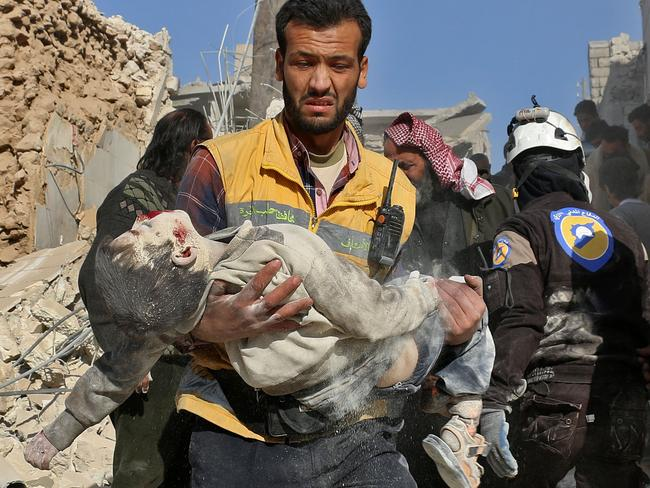A medic carries a boy from the rubble after a barrel bomb attack in Aleppo on November 24. Picture: Ameer Alhalbi/AFP
