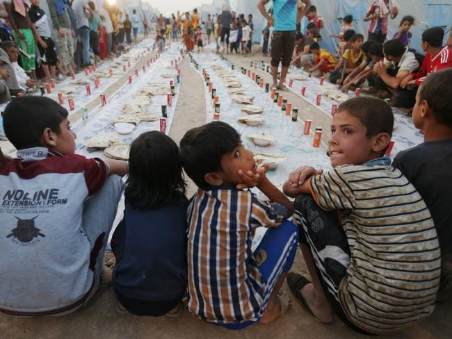 Displaced Iraqi boys wait for a sunset communal meal to break their fast during the first day of the Islamic holy month of Ramadan on Sunday in the Khazer area outside Irbil, northern Iraq. Photo: Hussein Malla
