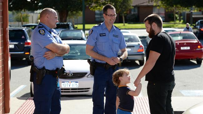 Constable Eddie Cuthbert and Sergeant Dean Kelland talk to shopper Toby King and his son Archie King, 3.