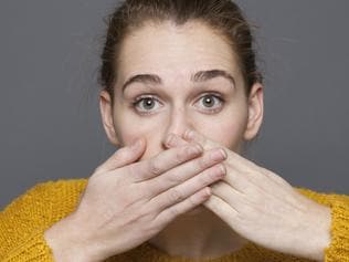 stunned young woman covering her mouth for mistake or regret