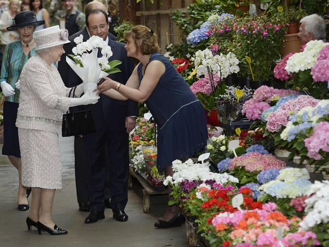In bloom...The Queen receives flowers as she visits the Paris Flower Market. Picture: Getty