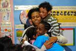 <p>US First Lady Michelle Obama is hugged by children as she visits Mary's Center, a non-profit organization which helps people with limited or no access to health services, in Washington on February 10, 2009.</p>