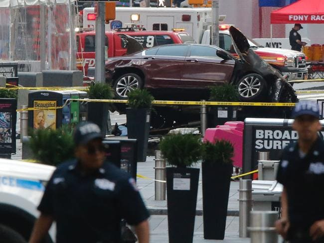 Police officers secure the area near the car after it plunged into pedestrians in Times Square. Picture: AFP.