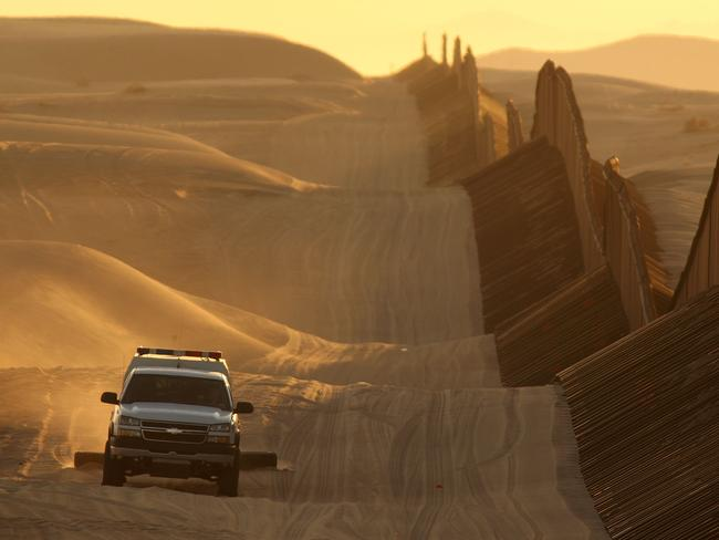 Slipping past ... A border patrol vehicle drags the sand to make any new footprints of border crosses more visible along a recently constructed section of the US-Mexico border fence.