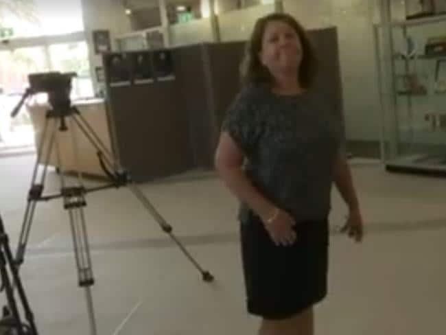 A staffer for Gold Coast Mayor Tom Tate tells an ABC news crew they're not welcome at today's press conference. Picture: ABC