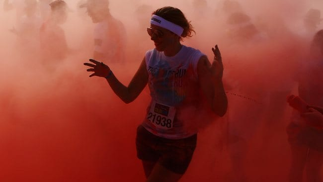 Competitors run through the pink colour throw area during the Colour Run. Picture: Getty