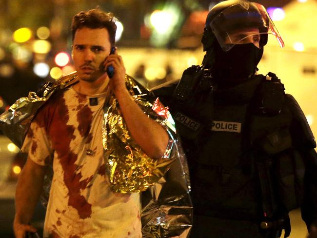 Attack ... A French policeman assists a blood-covered victim near the Bataclan concert hall following attacks in Paris in November. Picture: Reuters