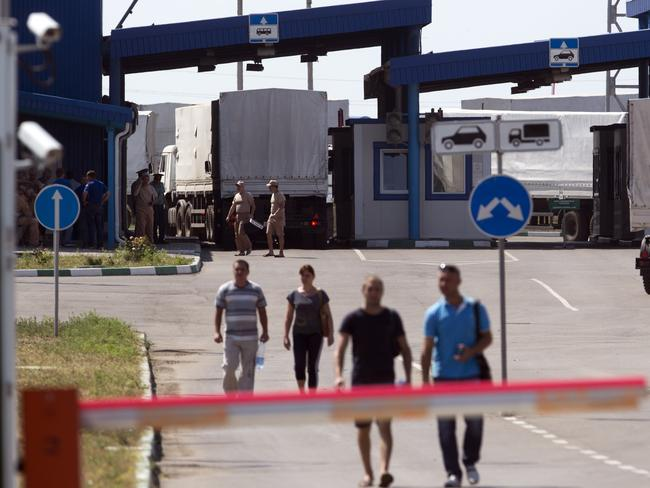 Trucks of the Russian aid convoy are searched at a Russian inspection zone inside a border control point with Ukraine in the Russian town of Donetsk. AP Photo/Pavel Golovkin