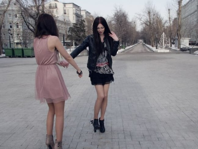 Husband and wife frolic in the street of Moscow, looking for all the world like identical twin sisters