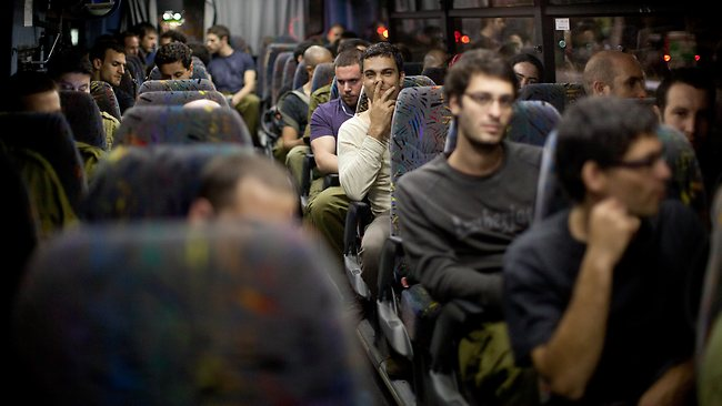 Israeli reserve soldiers sit on board a bus heading to south of the country after they were called for duty in Tel Aviv, Israel. Up to 75,000 reservists called up. (Photo by Uriel Sinai/Getty Images)