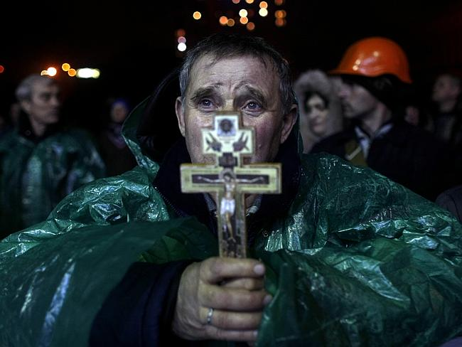 Prayers for a nation torn apart ... An anti-government protester holds a crucifix at Independence Square. Picture: AP Photo/ Marko Drobnjakovic