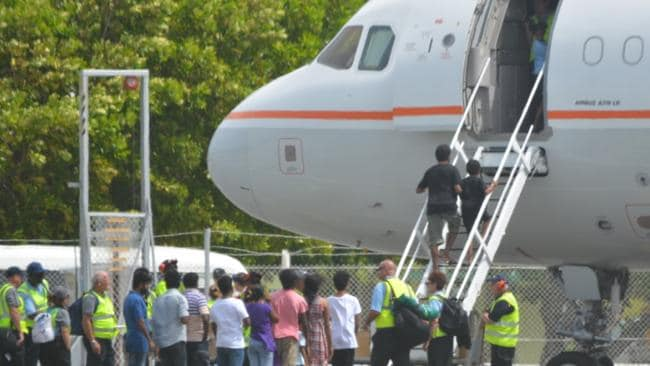 Long journey ... the asylum seekers prepare to board a plane at Cocos Island to fly to the Curtin Detention Centre.