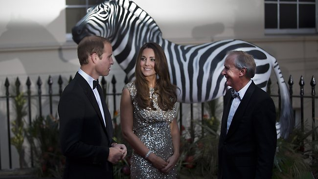 Britain's Prince William, left, and his wife Kate the Duchess of Cambridge are greeted as they arrive, in front of a model zebra, to attend the Tusk Conservation Awards at the Royal Society in London, Thursday, Sept. 12, 2013. The annual awards aim to recognize and celebrate outstanding achievement in the field of African conservation. (AP Photo/Matt Dunham)