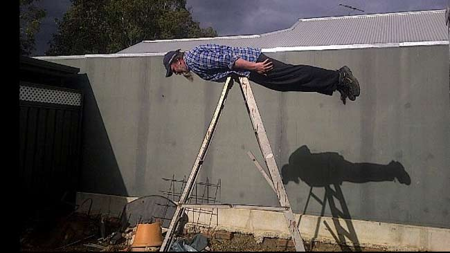 A man planks on a ladder in his backyard. Picture: Facebook