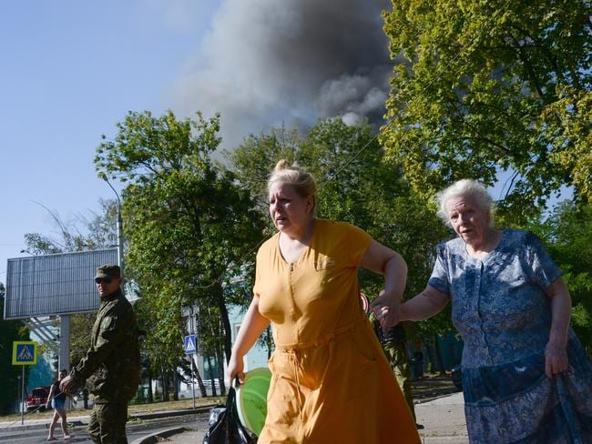 Running for their lives ... two women rush across the street after shelling in the town of Donetsk, eastern Ukraine, on Wednesday.