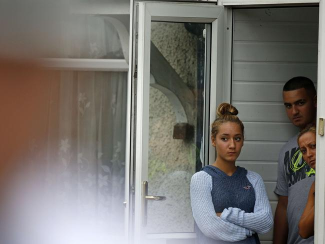 Scared locals look on ... as Police Commander Simon Letchford addresses a press conference on Nightingale Road in Edmonton, north London. Picture: AFP