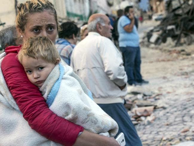 A woman holds a child as they stand in the street following the huge shake that could be felt in Rome. Massimo Percossi/ANSA via AP.