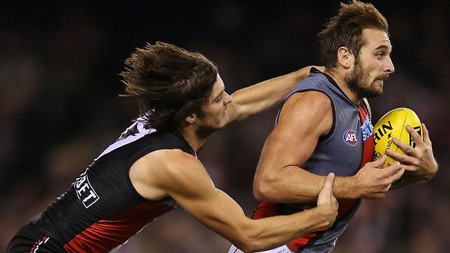 MELBOURNE, AUSTRALIA - APRIL 20: Jobe Watson of the Bombers runs with the ball away from Dylan Roberton of the Saints during the round four AFL match between the St Kilda Saints and the Essendon Bombers at Etihad Stadium on April 20, 2013 in Melbourne, Australia. (Photo by Michael Dodge/Getty Images)