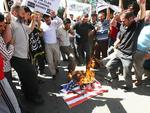 <p>Protesters burn a US flag in Ankara, Turkey. Picture: AFP</p>