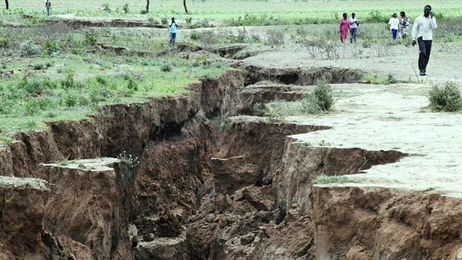 People walk past the deep split in the earth near the town of Mai-Mahiu in the Rift Valle in Kenya. Picture: AFP