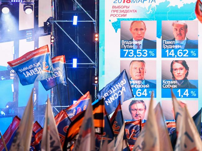 People wave flags in front of a huge screen displaying preliminary results of the presidential election. Picture: AFP/Mladen Antonov