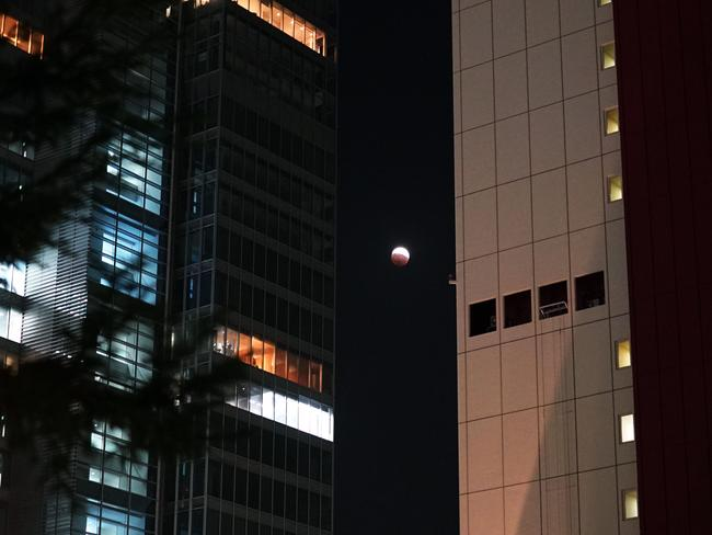 Blood moon ... the lunar eclipse is seen between two buildings in Tokyo. Picture: AFP