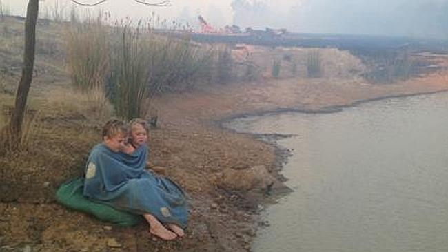 Helen Goudy's three children Austin, Tory and Royce - aged 2, 4 and 7 - huddle on a blanket by a neighbour's dam for an hour in Porcupine Court, Chintin, Victoria, as a fire races towards their home. Picture: Helen Goudy/ABC TV