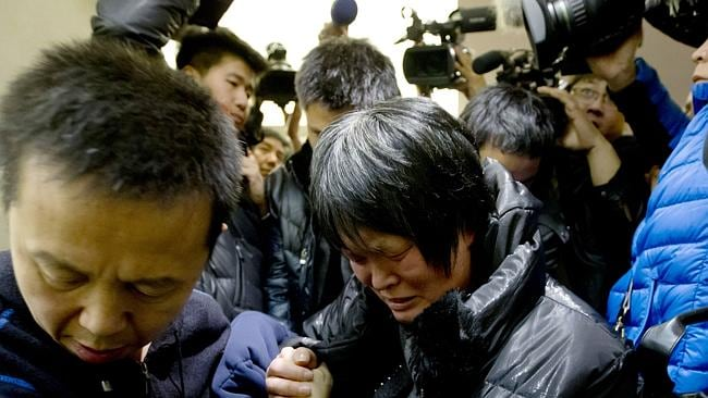 A Chinese woman cries as she leaves a hotel room for relatives or friends of passengers in Beijing.