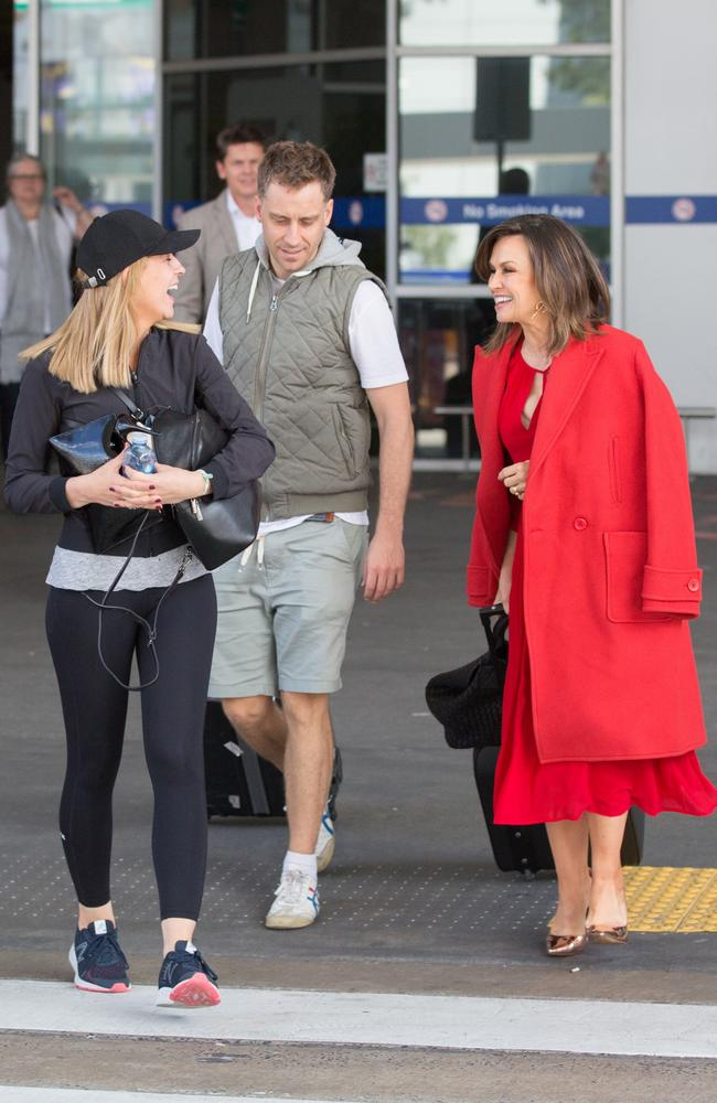 Lisa and Carrie laugh as they walk to separate waiting cars at Melbourne airport.