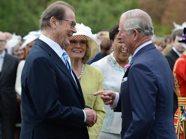 Prince Charles and Roger Moore chat during a garden party in 2016. Picture: Getty