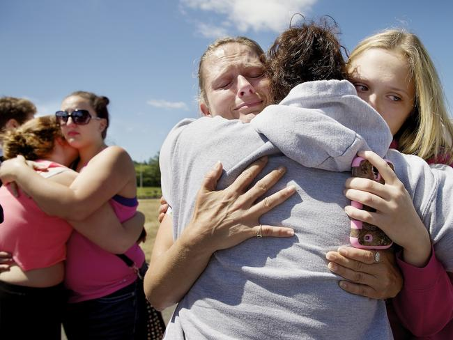 Brandi Wilson, left, and her daughter, Trisha Wilson, 15, right, embrace Trish Hall, a mother waiting for her student, after the Reynolds High School shooting in Oregon. Picture: AP/Troy Wayrynen