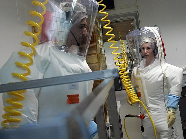 Researchers wearing protective gear work in the P4 European High Level Security Laboratory (EHLS) in central France.
