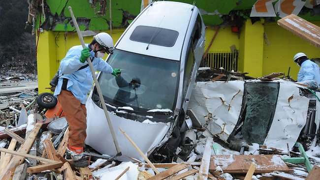 WIRE: Rescue workers search through debris in Minamisanriku, Miyagi prefecture on March 18, 2011. Japan was battling a nuclear and humanitarian crisis on as engineers worked to restore power to a stricken atomic plant, while the toll of dead and missing from the quake and tsunami topped 16,000. AFP PHOTO / MIKE CLARKE