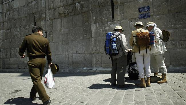 A Syrian police officer looks at German tourists as he walks past at the walls of the Old Town in Damascus in 2005. Picture: Ghaith Abdul-Ahad/Getty Images
