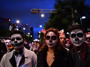 "People fancy dressed as ""Catrina"" take part in the ""Catrinas Parade"" along Reforma Avenue, in Mexico City on October 23, 2016. Mexicans get ready to celebrate the Day of the Dead highlighting the character of La Catrina which was created by cartoonist Jose Guadalupe Posada, famous for his drawings of typical local, folkloric scenes, socio-political criticism and for his illustrations of ""skeletons"" or skulls, including La Catrina. / AFP PHOTO / YURI CORTEZ"