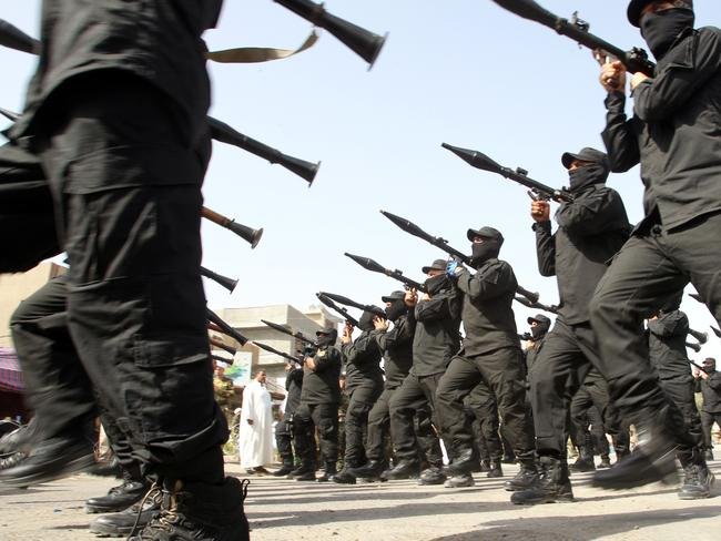 Strange bedfellows ... Shiite fighters parade with their weapons in Baghdad. Iraq's government is cooperating with them against a jihadist-led onslaught that Baghdad's forces are struggling to contain on their own. Picture: Ali Al-Saadi